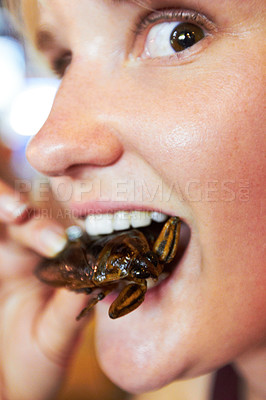 Buy stock photo Beautiful tourist biting into a fried cockroach