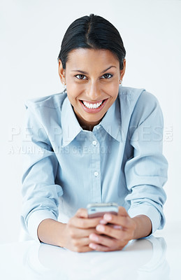 Buy stock photo Young female executive texting on mobile phone at desk