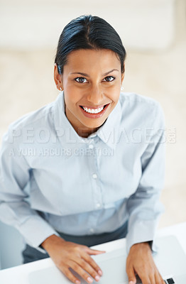 Buy stock photo High angle view of happy mixed race business woman using laptop in office