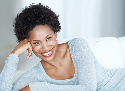 Buy stock photo Gorgeous young woman smiling while lying on couch