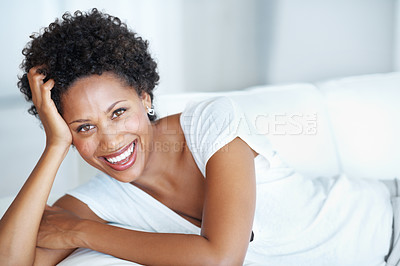 Buy stock photo Portrait of casually dressed young woman smiling while resting on couch