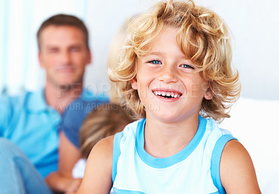 Buy stock photo Closeup of cute little boy smiling at home with family in background
