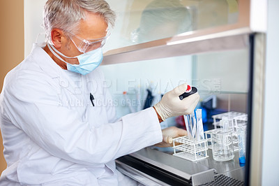 Buy stock photo Mature male scientist carrying out experiments in sterile environment at laboratory