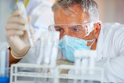 Buy stock photo Male scientist looking at test tube with liquid during scientific experiment in laboratory