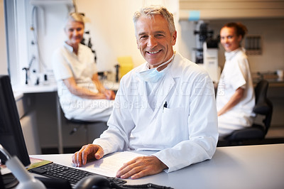 Buy stock photo Smiling male scientist with two female assistants in background at the laboratory