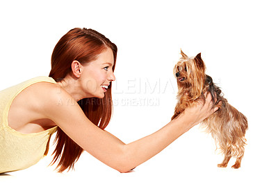 Buy stock photo A young woman lying on the ground and holding her yorkie up
