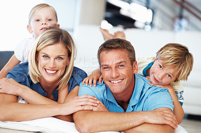 Buy stock photo Portrait of beautiful middle aged couple with two little kids relaxing at home