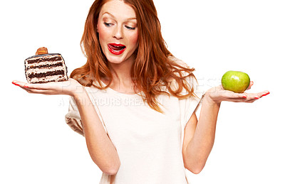 Buy stock photo A young redhead choosing cake over a healthy apple