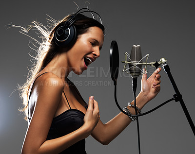 Buy stock photo Lovely young brunette gesturing while singing into a cardioid microphone