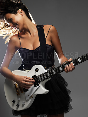 Buy stock photo Beautiful female guitarist shaking her hair to the rhythm while happily playing a white electric guitar