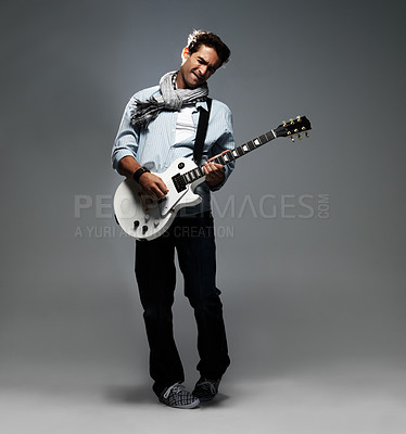 Buy stock photo Trendy young guitarist leaning back in concentration while playing a solo on his guitar - copyspace