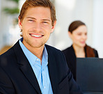 Closeup of a happy smart young business man with a colleague in the background