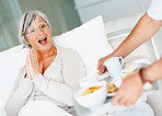 Surprised retired female being served breakfast in bed