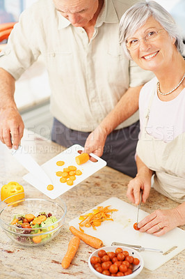 Smiling mature couple preparing food in the kitchen