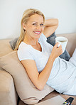 Beautiful woman drinking coffee relaxing on sofa