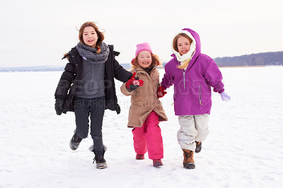 Buy stock photo Three young sisters running outside in the snow