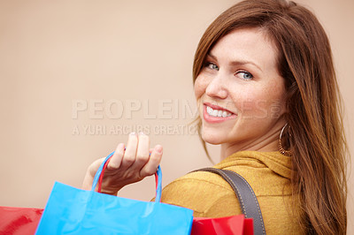 Buy stock photo Over the shoulder portrait of an attractive young woman holding shopping bags