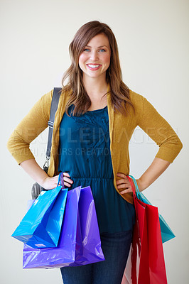 Buy stock photo Pretty young woman smiling at the camera while carrying colourful shopping bags