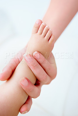 Buy stock photo Cropped close up shot of a mother holding her baby's foot