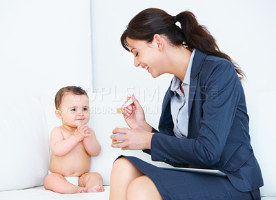 Buy stock photo Shot of a busy working mom spoon feeding her baby while a digital tablet rests on her lap