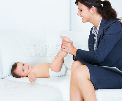 Buy stock photo Shot of a working mom happily changing her baby daughter's diaper