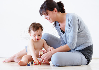 Buy stock photo Shot of a cute young baby and mother playing with alphabet blocks