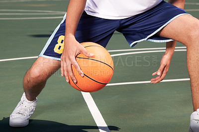 Buy stock photo A basketball player passes the ball between his legs