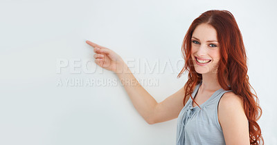 Buy stock photo A young woman pointing at copyspace