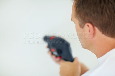 Closeup of a man drilling a hole in wall
