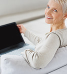Smiling elderly woman working on a laptop at home