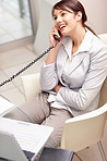 Happy business woman having a conversation over the telephone