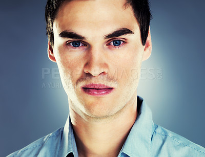 Buy stock photo Closeup portrait of a smart young guy looking serious against grey background