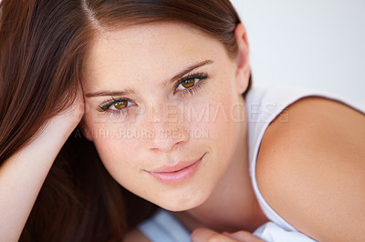Buy stock photo A gorgeous young woman smiling while leaning on her arm