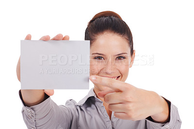 Buy stock photo Studio portrait of an attractive young woman pointing at a small blank sign she is holding isolated on white