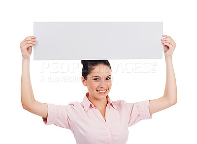 Buy stock photo Shot of a happy-looking young women holding up a blank banner over her head isolated on white