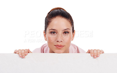 Buy stock photo Studio shot of an attractive young women peering over a bank placard isolated on white