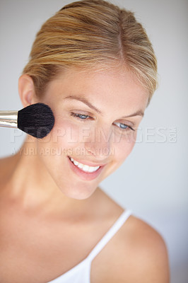 Buy stock photo Closeup shot of an attractive young woman applying makeup with a brush