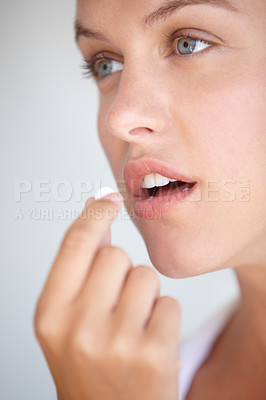 Buy stock photo Closeup shot of a young woman taking a vitamin