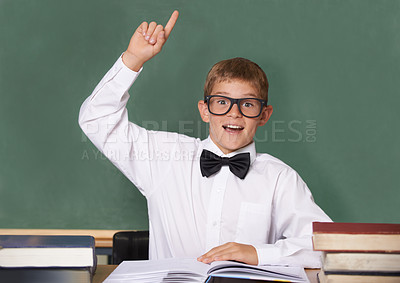 Buy stock photo A schoolboy wearing a bow-tie and glasses raising his hand to answer a question - portrait