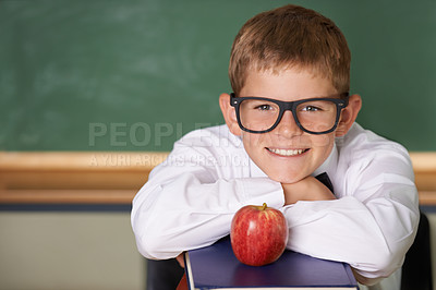 Buy stock photo A happy schoolboy wearing glasses leaning on a pile of books and smiling at the camera