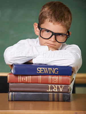 Buy stock photo A frowning young schoolboy looking at the camera while leaning on a pile of books