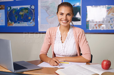 Buy stock photo A lovely young teacher sitting at her desk and smiling at the camera