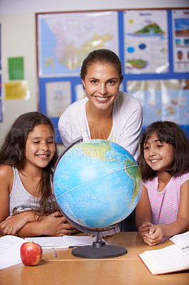 Buy stock photo A teacher and two multi-ethnic schoolgirls sitting alongside a globe and smiling at the camera