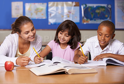 Buy stock photo A young teacher sitting with her two ethnic pupils while they study