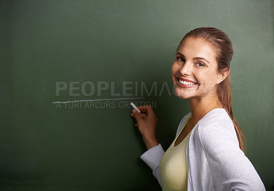 Buy stock photo A beautiful young teacher writing on a blackboard while smiling at the camera