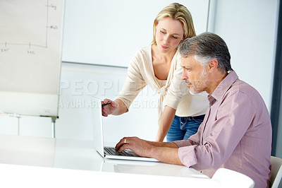 Buy stock photo Shot of two designers working on a laptop together and talking