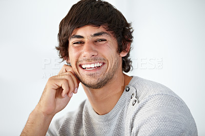 Buy stock photo Handsome young man smiling and laughing while against a white background