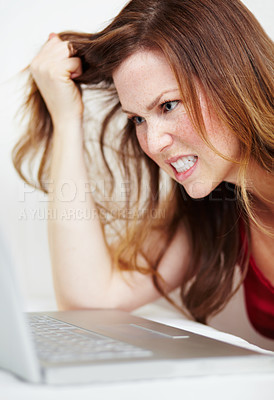 Buy stock photo A frustrated young woman pulling her hair out while working on a laptop