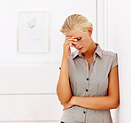 Depressed woman leaning against a wall