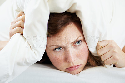 Buy stock photo A grumpy looking woman lying in bed with a pillow over her head